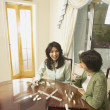 Stock Photo: Asian mother and adult daughter playing dominoes