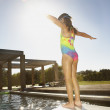 Little girl standing on the end of a diving board — Stock Photo