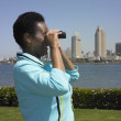 African woman using binoculars with cityscape in background — 图库照片