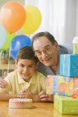 Hispanic grandfather and grandson hugging near birthday gifts — Stock Photo
