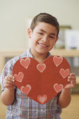 Hispanic boy holding paper heart — Stock Photo
