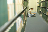 Young woman reading in a library — Stock Photo