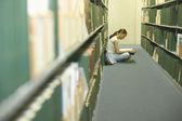 Mujer joven en una biblioteca de lectura — Foto de Stock