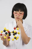 Asian female scientist looking at chemical model — Stock Photo