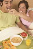 Young woman feeding boyfriend breakfast in bed — Stock Photo