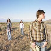 Three standing in desert — Stock Photo