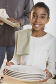 Portrait of girl drying dishes with father — Stock Photo