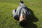South American businessman laying in grass — Stock Photo