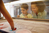 Mother and son watching through ice cream case window — Stok fotoğraf
