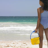 Rear view of girl with bucket at beach — Stock Photo