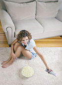 Hispanic woman eating popcorn and changing channel with remote control — Stock Photo