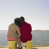 Couple sitting and hugging next to water — Stockfoto