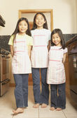 Three young Asian sisters wearing aprons in the kitchen — Stock Photo