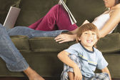 Young boy smiling next to parents on sofa — Stock Photo