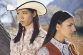 Young women in cowboy outfits posing for the camera — Stock Photo