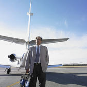 Indian businessman standing next to airplane — Stock Photo