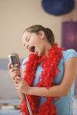 Hispanic girl singing into microphone in bedroom — Stock Photo