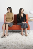 Young women ignoring each other on couch — Stock Photo