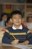 Portrét chlapce u stolu s školní práce — Stock fotografie