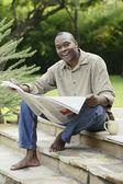 Man reading newspaper outdoors — Stock Photo