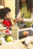Jeune garçon afro-américain dans le panier d'achat à la caisse du supermarché — Photo