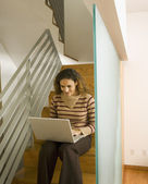Woman looking at laptop on stairs — Stock Photo