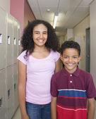 Dívka a chlapec s úsměvem na školní chodbě — Stock fotografie