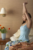 Woman stretching on side of bed — Stock Photo