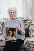 Senior woman holding photograph — Stock Photo