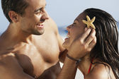South American man holding starfish in girlfriend's hair — Stock Photo