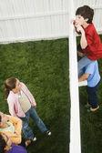 Meninos de raça mista, olhando por cima da cerca para meninas — Foto Stock