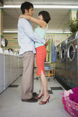 Couple hugging at laundromat — Stock Photo