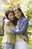 Sisters hugging and smiling for the camera — Stock Photo