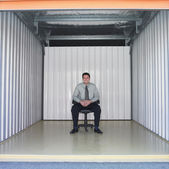Businessman sitting in empty storage space — Stock Photo