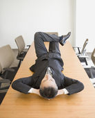 Businessman lying on table — Stock Photo