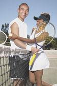 Portrait of couple hugging on tennis court — Stock Photo