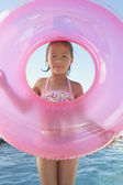 Young girl holding an inner tube — Stock Photo