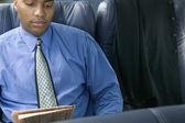 Businessman reading newspaper on airplane — Stock Photo