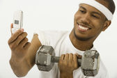 African man holding dumbbell and cell phone — Stock Photo
