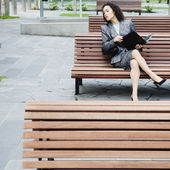 Businesswoman sitting on park bench — Stockfoto