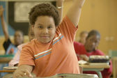 Young boy raising his hand in classroom — Stock Photo
