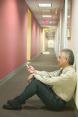 Businessman sitting on floor and using cell phone — Stock Photo