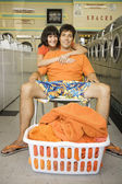 Woman hugging relaxed boyfriend in a laundromat — Stock Photo