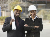 African American businesspeople with blueprints — Stock Photo