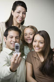 Hispanic family taking self-portrait with cell phone — Stock Photo