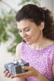 Woman holding gift while smiling — Stock Photo