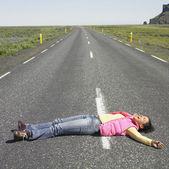 Jovem mulher deitada no meio da estrada a rir — Foto Stock
