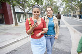 Girlfriends walking down the city street together — Stock Photo