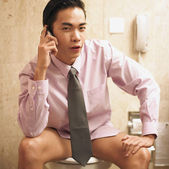 Businessman talking on phone while sitting on toilet — Стоковое фото