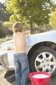 Young boy washing car — Stock Photo